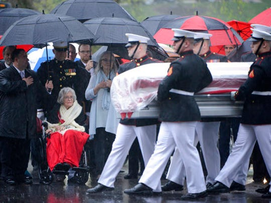 In this U.S. Army photo by Rachel Larue/Arlington National Cemetery, Annie Glenn, seated, widow of John Glenn, watches as members of the U.S. Marine Corps from Marine Barracks Washington carry the casket of her husband during his graveside service at Arlington National Cemetery in Arlington, Va. Thursday, April 6, 2017. Glenn, who died Dec. 8 at age 95, was laid to rest in a private burial attended by relatives and invited guests. His family scheduled the service for what would have been John and Annie Glenn's 74th wedding anniversary. (U.S. Army photo by Rachel Larue/Arlington National Cemetery via AP)