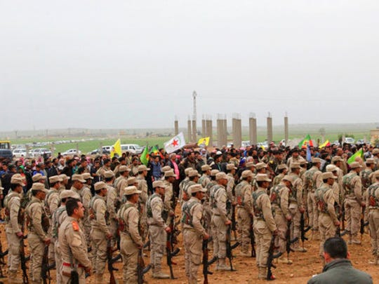 This photo provided by Hawar News Agency, a Kurdish-run news agency, which has been authenticated based on its contents and other AP reporting, shows fighters from the predominantly-Kurdish Syrian Democratic Forces attending  the funeral procession of 18 of their comrades, who were killed Tuesday by a misdirected airstrike by the U.S.-led coalition, in Tal al-Abyad, northeast Syria, Thursday, April 13, 2017. U.S. Central Command said coalition aircraft were given the wrong coordinates by their partner forces, the Syrian Democratic Forces, for a strike intended to target Islamic State militants south of their Tabqa stronghold.