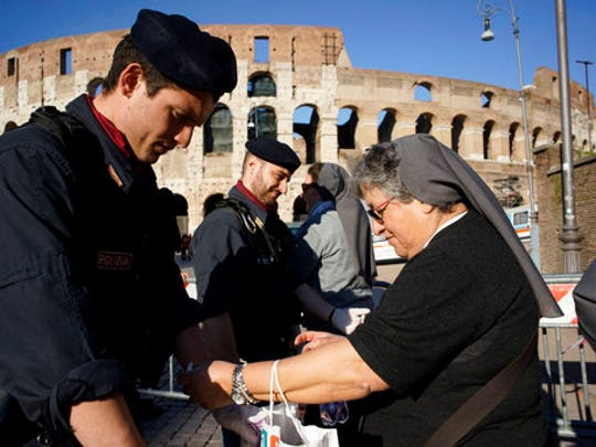 A police officer checks the bag of a nun in the area around the ancient Colosseum a few hours ahead of the Way of the Cross procession, in Rome, Friday, April 14, 2017. Thousands of pilgrims are expected to flood the area surrounding the Colosseum to listen to the words of Pope Francis and watch the march leading to the cross.