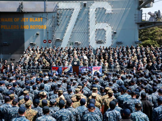U.S. Vice President Mike Pence, center, speaks to U.S. servicemen and Japanese Self-Defense Forces personnel on the flight deck of U.S. navy nuclear-powered aircraft carrier USS Ronald Reagan, at the U.S. Navy's Yokosuka base in Yokosuka, south of Tokyo, Wednesday, April 19, 2017. Japan is drawing up emergency responses in case of a North Korea missile strike. A number of municipalities are testing community alarm systems and planning evacuation drills as concerns run high around U.S. military bases. Both Japan and South Korea are home to tens of thousands of U.S. troops.