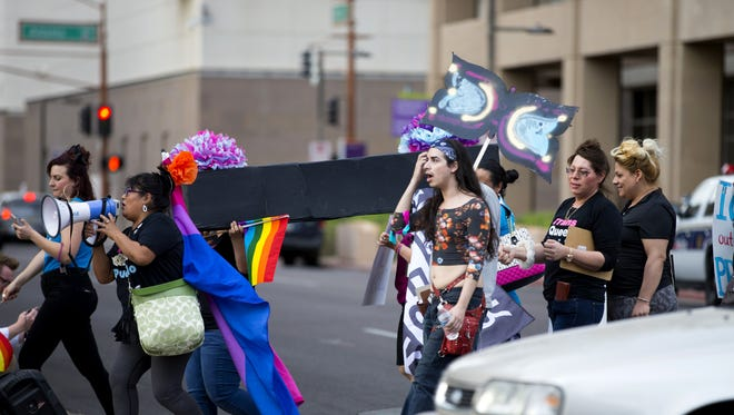 The LGBTQ and people of color walk in downtown Phoenix during a funeral procession to honor those that were killed by the Phoenix Police Department.