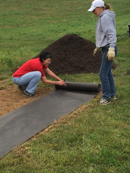 Aleshia Hawkins, left, works with another volunteer to prepare for an Eagle Scout project Saturday morning at West Manheim Township Park.