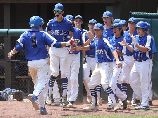 Tyler Diamond is greeted at the dugout by team mates as he scores the first run of the game by Middlesex.