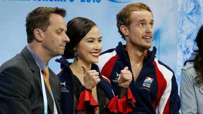 Madison Chock, center, and Evan Bates, right, of the Novi Ice Arena react after the short dance at the  ISU World Figure Skating Championships in Shanghai on Wednesday, March 25, 2015.
