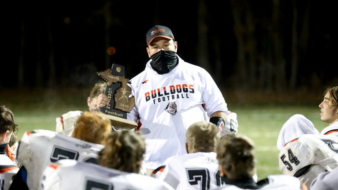 Summerfield football coach Alex Lipka holds the District championship trophy as he talks to his team after a win over Whiteford on Nov. 13. The Bulldogs hope to resume their state playoff run with a game against Clarkston Everest Collegiate on Dec. 15.