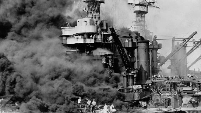 In this Dec. 7, 1941 photo made available by the U.S. Navy, a small boat rescues a seaman from the USS West Virginia burning in the foreground in Pearl Harbor, Hawaii, after Japanese aircraft attacked the military installation. More than 2,300 U.S. service members and civilians were killed in the strike which brought the United States into World War II.