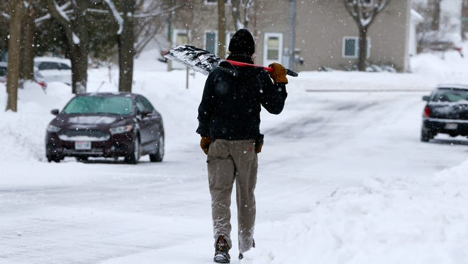 A person walks with his shovel Monday, April 16, 2018, in Wausau, Wisc. T'xer Zhon Kha/USA TODAY NETWORK-Wisconsin