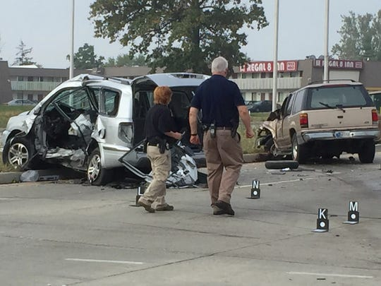Investigators assess the crash scene Tuesday at Washington Street and High School Road.