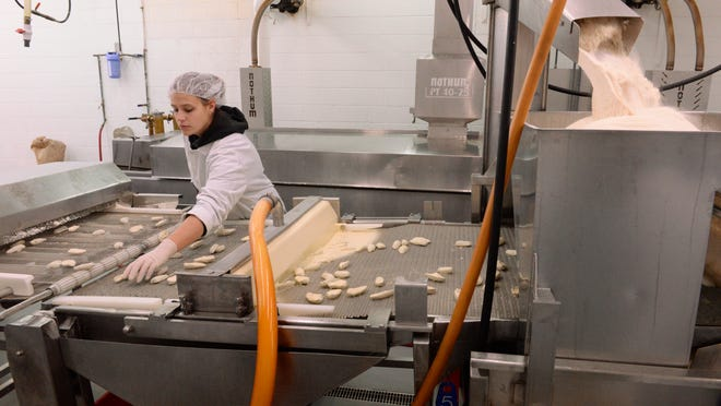 Tatum Komorowski separates each cream cheese jalapeno snapper as it goes through the breading line at Riverside Foods in Two Rivers. The family-owned company specializes in making appetizers and seafood for distribution nationally and overseas