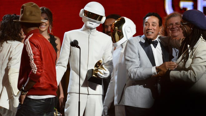 Daft Punk, in white, Pharrell Williams in red and Nile Rodgers, beret, receive the Record of the Year Grammy.