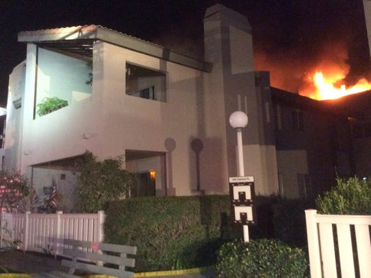 Flames erupt from the attic of an apartment building in Thousand Oaks on Thursday night in a fire that displaced up to 20 residents.