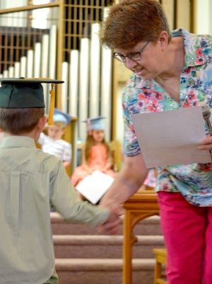 Holly Senft, preschool director for St. Paul Evangelical Lutheran Church in North Codorus Township, hands a certificate to a student at preschool graduation. The church hopes to be able to make its preschool program free next year.