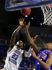 LA Tech's Xavian Stapleton tries to block a shot by MTSU's Marcus Tarrance in the second half of Saturday's game.