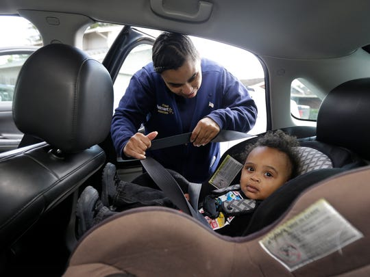 Shannon Henderson buckles her son, Justin, 1, into his car seat for the ride to his father's house before she goes to work.