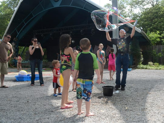 Greg Lloid, a volunteer at the Alexandria Zoo, entertains children by making bubbles at Water Play Day held Saturday. Children played on water slides, in sprinklers and learned about oceans and rivers.