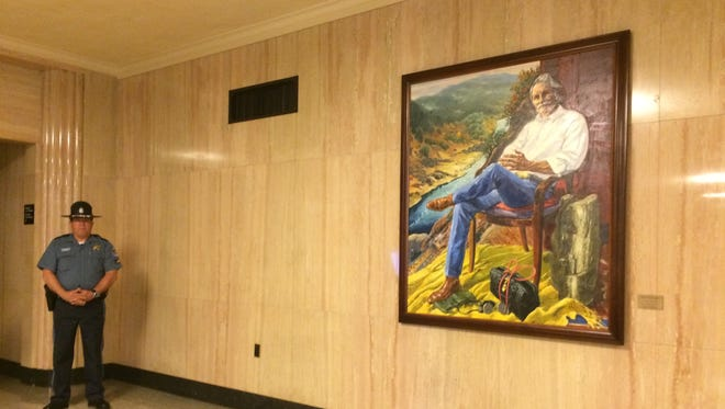 The official portrait of former Gov. John Kitzhaber hangs outside the Senate chambers, where lawmakers voted Wednesday to preserve the Oregon Health Plan. Kitzhaber, a physician, founded the health plan in the early 1990s.