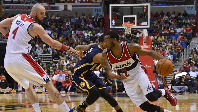 Washington Wizards guard John Wall (2) dribbles past Indiana Pacers guard George Hill (3).