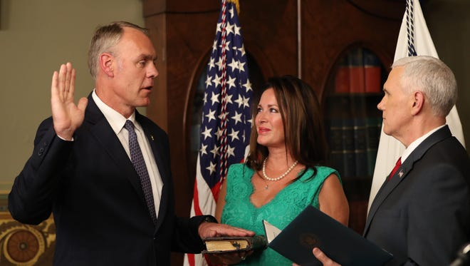 Vice President Mike Pence administers the oath of office to Interior Secretary Ryan Zinke on Wednesday in the Eisenhower Executive Office Building on the White House complex in Washington, as his wife, Lolita, holds the Bible.