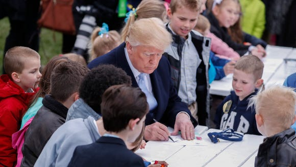 President Donald J. Trump signs his autograph for children