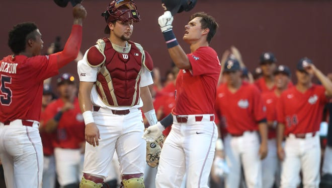 Samford's Troy Dixon, left, high-fives teammate Brooks Carlson after his two-run home run as FSU's Cal Raleigh looks on during their NCAA Regional game at Dick Howser Stadium in Tallahassee, Fla. On Friday, June 1, 2018.