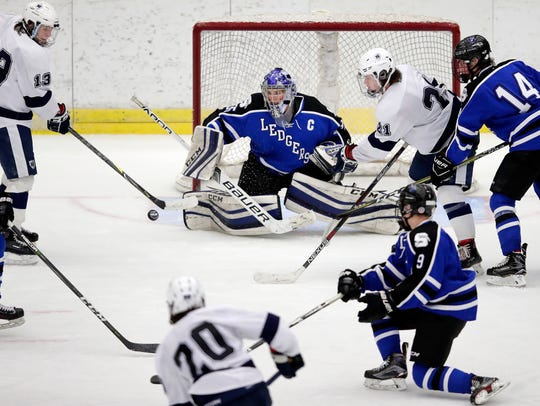 Hudson's Ben Lundeen takes a shot on Saint Mary's Springs goalie Colin Ahern in a WIAA state boys hockey quarterifinal TThursday at the Veterans Memorial Coliseum