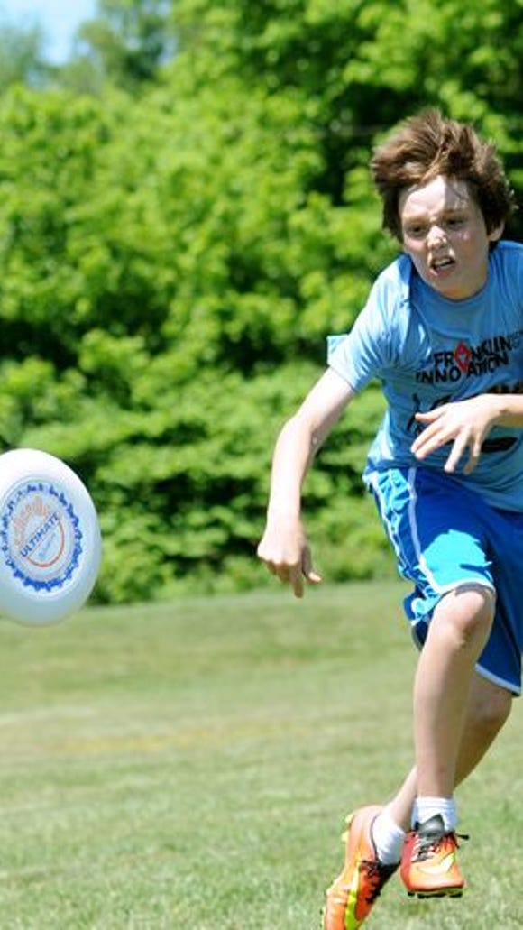 Alex Harkness, 12, a 6th grade student at The Franklin School of Innovation, leaps to block a pass as he plays in the ultimate frisbee competition at the Mountain Sports Festival at Carrier Park on Saturday, May 23.