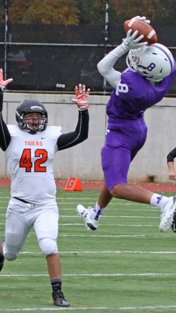 New Rochelle's Romeo Holden hauls in a reception over Mamaroneck's Justin Poniros during a Class AA quarterfinal football game at New Rochelle game Oct. 24, 2015. New Rochelle defeated Mamaroneck 28-20.