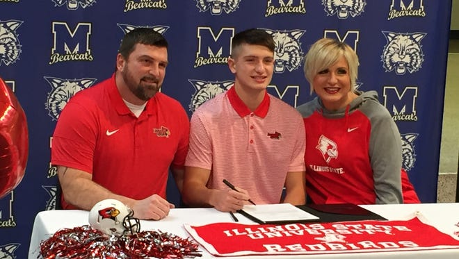 Trenton Hatfield signs his letter of intent with Illinois State, flanked by his parents Bobby and Lynne.