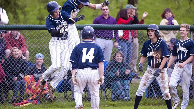 The Burlington Seahorses celebrate the go-ahead run by Chris Fenimore, left, and RBI by Eli Pine (14) during the third inning against Champlain Valley in the Division I high school baseball quarterfinals on Saturday afternoon in Hinesburg.