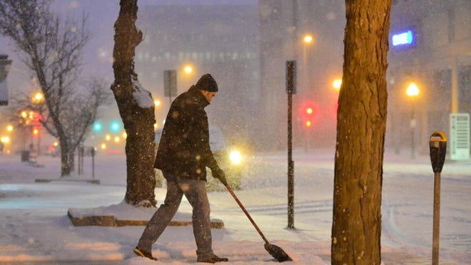 A man shovels the sidewalk in front of the GAR Hall in Peoria in a photo from the Journal Star archives.