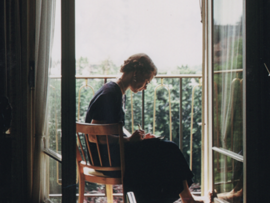 Louise Tostenrud, writing in her journal on a balcony