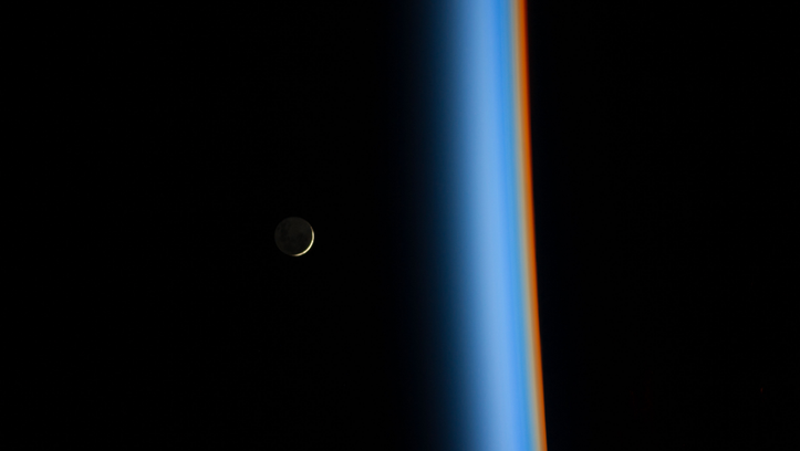 A crescent moon rising and the Earth's atmosphere. Distinct colors are visible because the dominant gases and particles in each layer of the atmosphere act as prisms, filtering out certain colors of light.