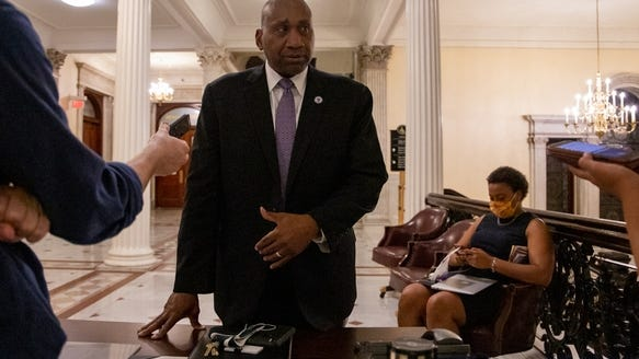 State Rep. Russell Holmes, a past chairman of the Black and Latino Legislative Caucus, spoke to reporters after the end of the marathon session while Rep. Nika Elugardo sat nearby.