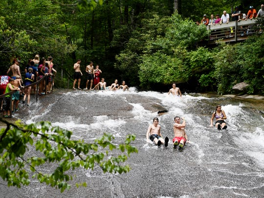 People take turns cooling off by going down Sliding Rock in the Pisgah National Forest in Brevard June 21, 2018.