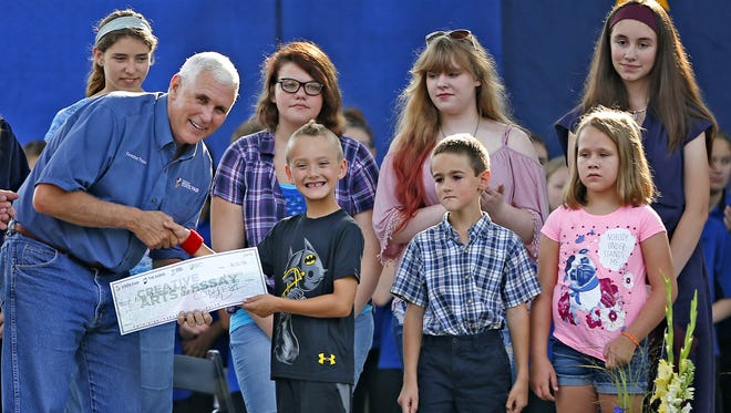 Gov. Mike Pence hands out awards for the Creative Arts and Essay contest to winners, including a smiling Ivan Wojciechowski, during the opening ceremony of the Indiana State Fair on Friday, Aug. 5, 2016.