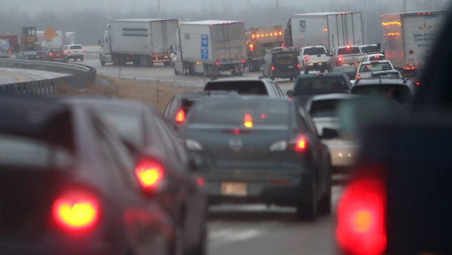 Slick roads made morning commutes tricky and slow, Tuesday morning, December 2, 2014, like this bumper-to-bumper traffic on inbound I-70 east on the west side.  Police agencies reported slide-offs causing traffic snags and road closures, and warned of crashes and slick spots on interstates and surface streets. Indianapolis had more than 60 plow trucks on city streets, the Department of Public Works said.