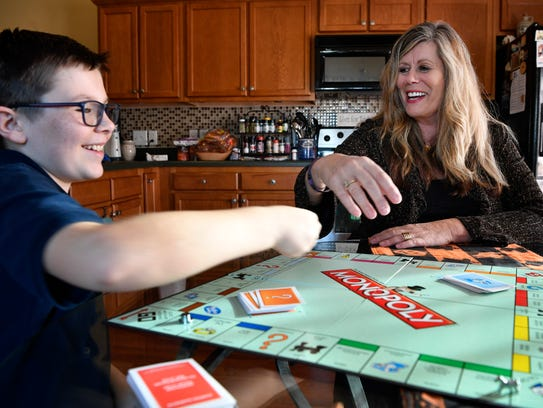 Jacqueline Perrine plays monopoly with her grandson,