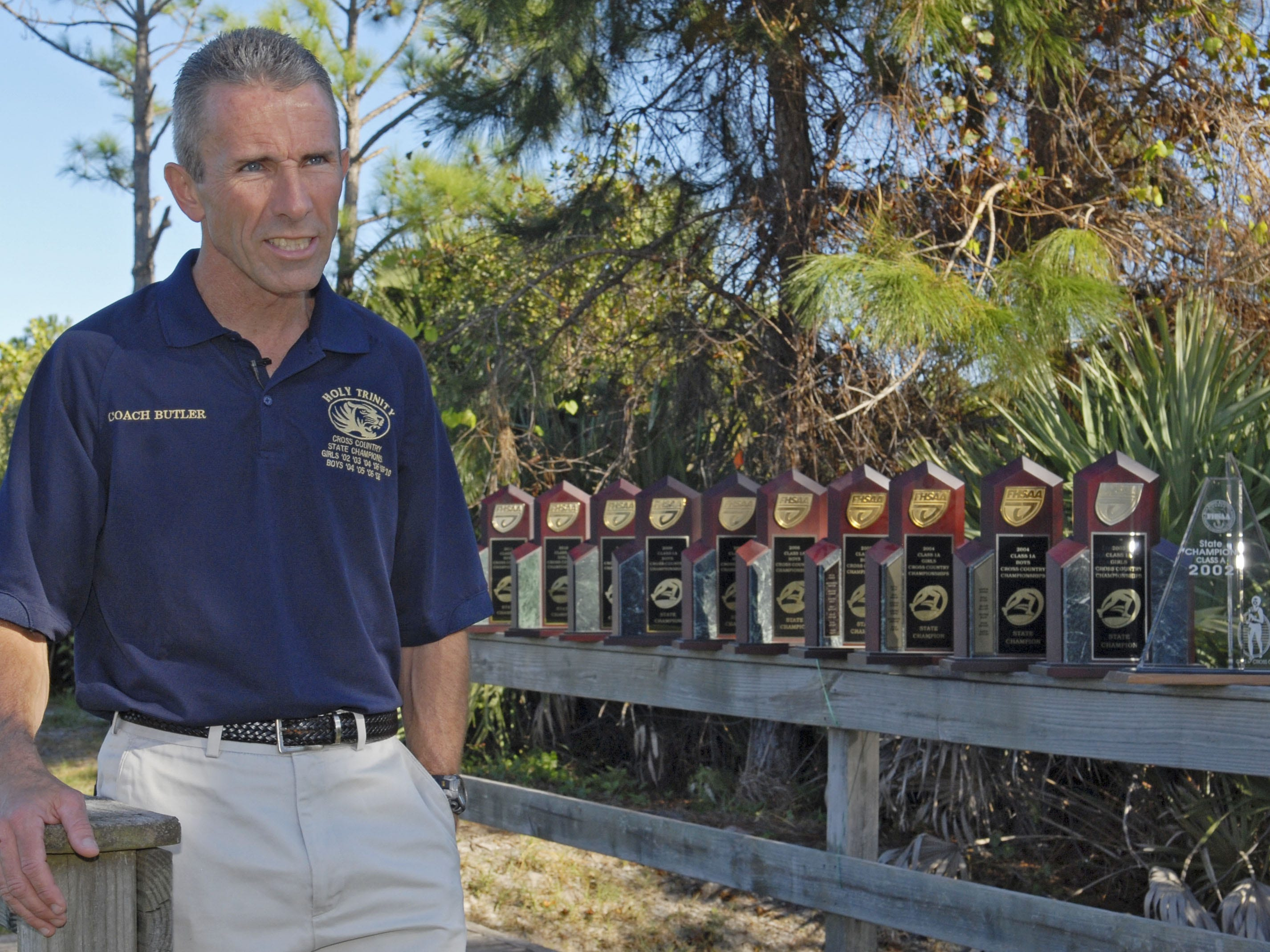 Doug Butler, coach at Holy Trinity Academy in Melbourne, with the state trophies his runners have won.
