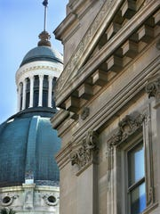 The dome of the Indiana Statehouse is seen behind part of the building's lower exterior facade.
