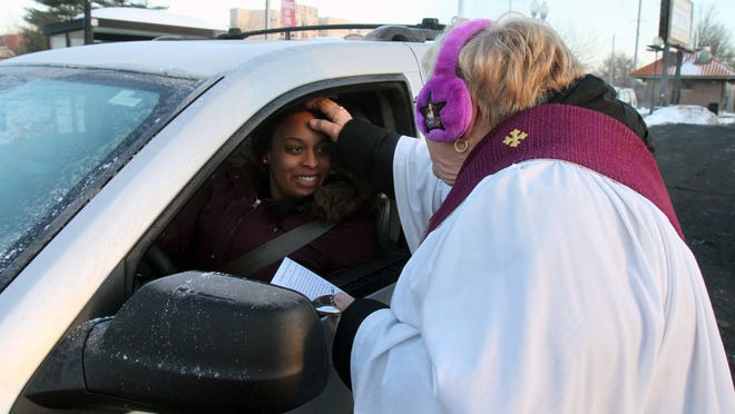 Deacon Kathleen DeJohn (right) gave Ash Wednesday offerings to commuters at the Perth Amboy train station, including a few that drove up in their cars to the station, on Wednesday.