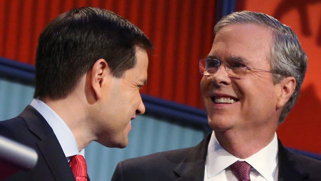 FILE - In this Aug. 6, 2015 file photo, Republican presidential candidates Marco Rubio, left, and Jeb Bush talk during a break during the first Republican presidential debate at the Quicken Loans Arena in Cleveland.