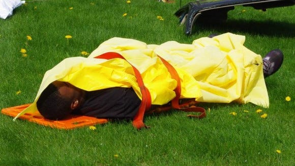 """A """"dead"""" Webster Thomas student lies in the grass after being pulled from the car in the mock crash demonstration several years ago. (M. Rosenberry)"""