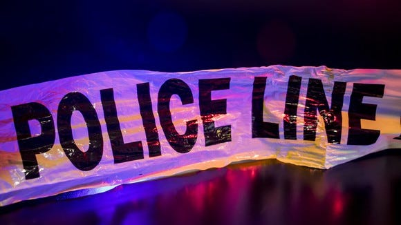 "Crime tape reading ""police line,"" backlit by blue and red lights."