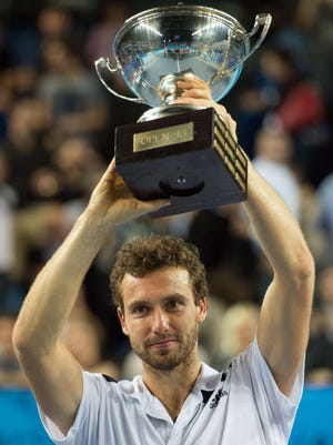 Latvia's Ernests Gulbis poses with his trophy after defeating France's Jo-Wilfried Tsonga during their Open 13 final match.