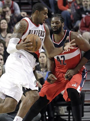 Blazers forward LaMarcus Aldridge uses his healthy right hand to drive past Wizards big man Nene in Saturday's victory.