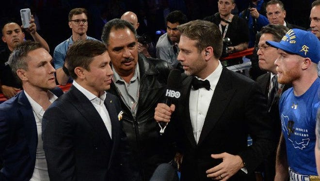 Gennady Golovkin and Canelo Alvarez, in the blue cap, talk to ESPN host Max Kellerman after they announced their fight in September