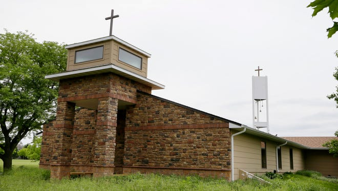 A cellphone tower inside the bell tower, rear right, is seen over the Resurrection Lutheran Church in Ankeny, Iowa. As wireless companies fill gaps in their networks, many have sought to camouflage the ungainly outdoor equipment that carries the nation's daily diet of calls, text messages and data.