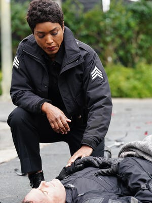 """LAPD cop Athena Grant (Angela Bassett) arrives at the scene of an injured motorcyclist (Andy Buckley) in the Season 1 finale of Fox's """"9-1-1."""""""