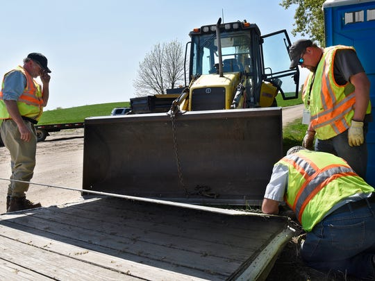 Sauk Rapids-based Minnesota Department of Natural Resources parks and trails crew members attach a floating dock to a backhoe for installation May 5 at the public boat landing on Two Rivers Lake near St. Anna.
