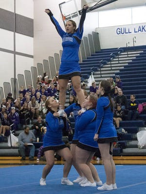 The Harper Creek High School Competitive Cheer team lifts one of it's flyers into the air at the Gull Lake Invitational on Jan. 14.